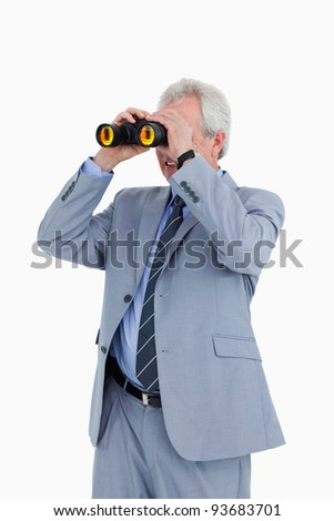 Mature tradesman looking through spy glass against a white background - stock photo