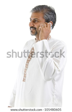 Mature traditional Indian man talking on mobile phone, isolated on white background - stock photo