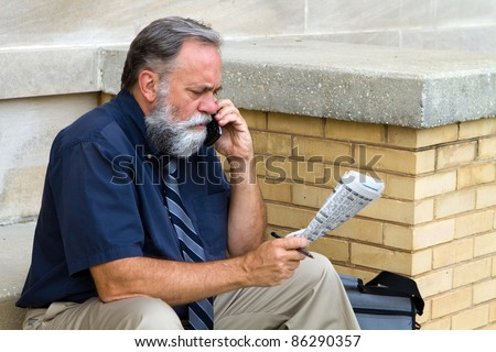 Mature unemployed salesman makes a call on his cell phone to reply to a advertisement for a want ad job in the newspaper. - stock photo