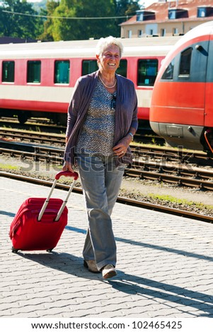 mature vital elderly couple at the railway station. travel on holiday - stock photo