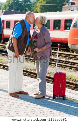 mature vital elderly couple at the train station. traveling on vacation - stock photo