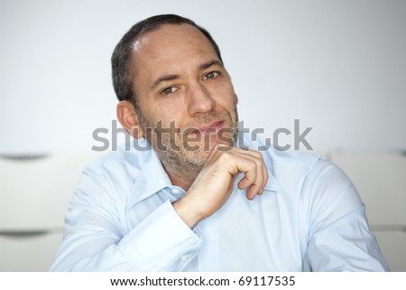 mature well dressed businessman is pointing into the camera