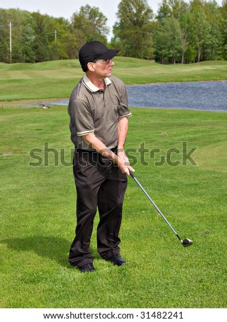 Mature well-dressed man golfing on golf course.