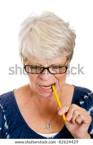 Mature white haired woman thinking hard while chewing on a pencil. - stock photo