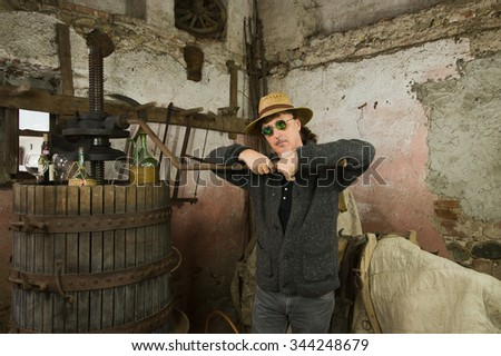 Mature winemaker and grapes press in old winery  - stock photo