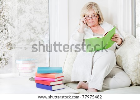 Mature woman adjusts her glasses while reading - stock photo