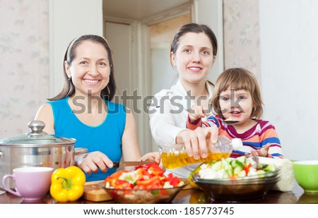 Mature woman and adult daughter with girl cooking vegetables salad at home - stock photo