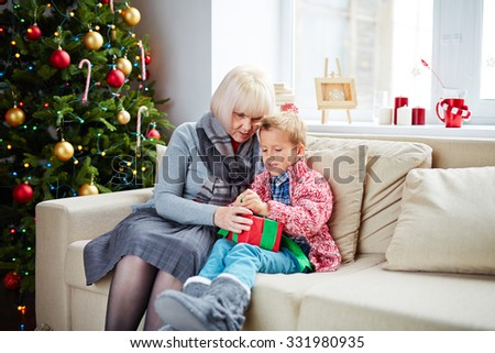 Mature woman and her grandson with gift sitting on sofa by Christmas tree