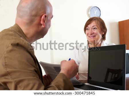 Mature woman answer questions of outreach worker with laptop at table in home or office - stock photo