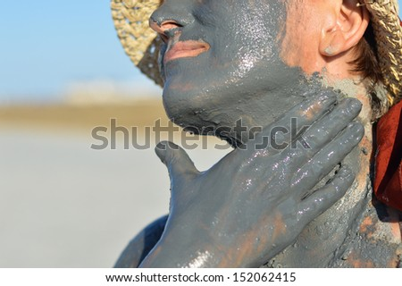 Mature woman applying mud on face and hands outdoors - stock photo