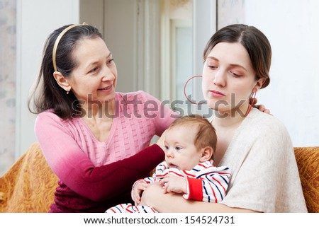 Mature woman asks for forgiveness from adult daughter with baby after quarrel - stock photo