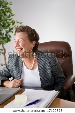 Mature woman at her desk in an office laughing uproariously. - stock photo