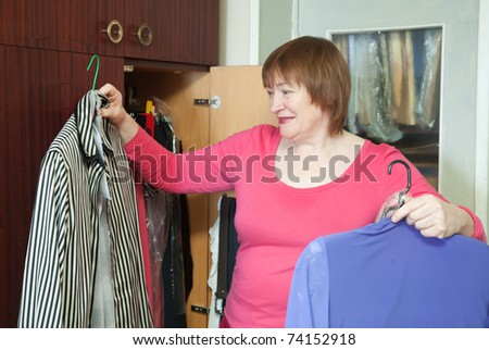 Mature woman at wardrobe. She thinking what get dressed. - stock photo