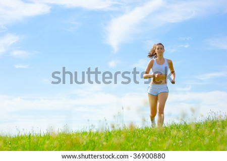 Mature woman athlete practicing in a spring meadow, from a complete series.