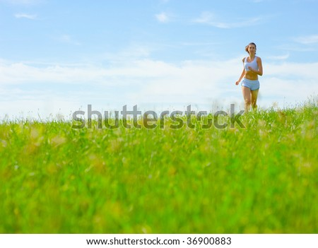 Mature woman athlete practicing in a spring meadow, from a complete series. - stock photo