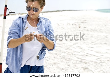 Mature woman baiting her fishing hooks at the beach; she's catching pompano! - stock photo