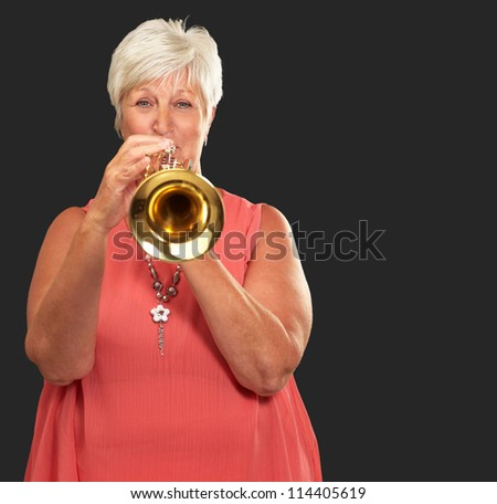 Mature Woman Blowing Her Trumpet Isolated On Black Background - stock photo