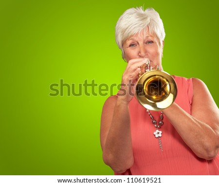 Mature Woman Blowing Her Trumpet Isolated On Green Background - stock photo