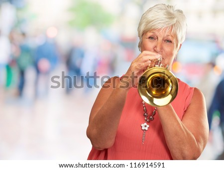 Mature Woman Blowing Her Trumpet, Outdoor - stock photo