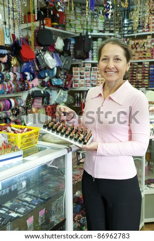 Mature woman  buying lipstick at cosmetics  shop