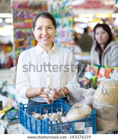 mature woman buys garlic for planting on the market - stock photo