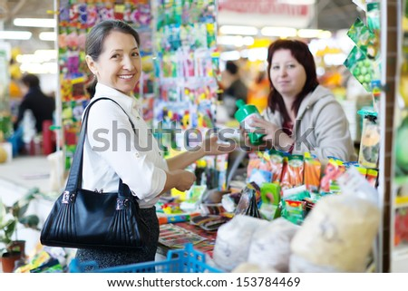 mature  woman buys liquid fertilizer at store for gardeners - stock photo