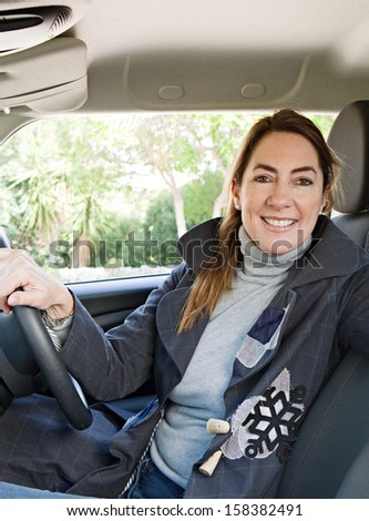 Mature woman car owner being happy and smiling in her new transport car, turning to camera and smiling during a sunny winter day while parked on a country road, car interior. - stock photo