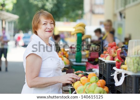 Mature woman chooses fruits at market