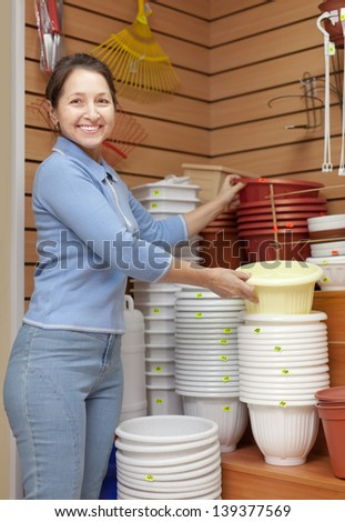 Mature woman chooses plastic flower pot in the store for gardeners - stock photo
