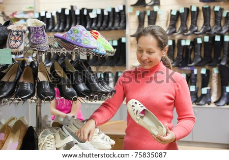 Mature woman chooses shoes at shoes shop - stock photo