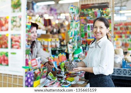 mature woman chooses solid fertilizer  at market - stock photo