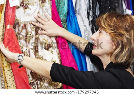 Mature  woman choosing clothes in the shop. - stock photo