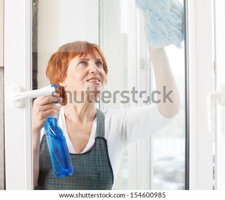 Mature woman cleaning window. Female washing window - stock photo