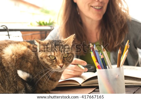 Mature woman coloring and drinking white wine - stock photo
