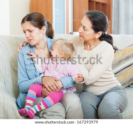 Mature woman comforting adult daughter with toddler at home