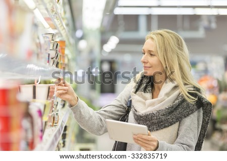 Mature woman comparing the price of yogurt with tablet pc - stock photo