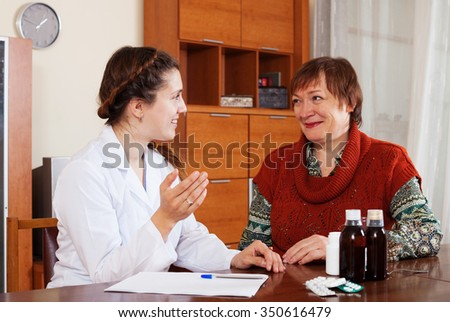 mature woman complaining  to friendly doctor about symptoms of ill at table - stock photo