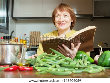 mature woman cooking okra with  cookbook in domestic kitchen - stock photo