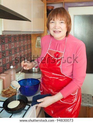 Mature woman cooking pancake at her kitchen