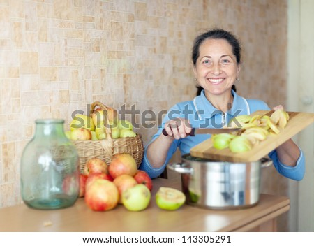 Mature woman cooks applesauce jam in kitchen - stock photo