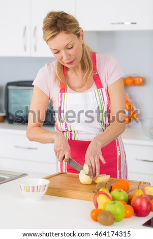 mature woman cuts fresh fruits in her kitchen at home