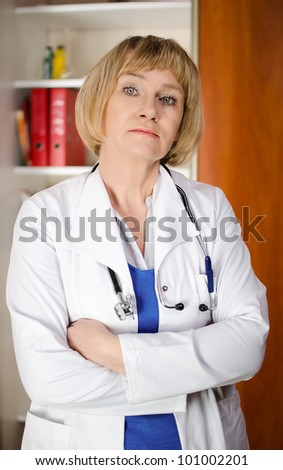 Mature woman doctor in white coat standind in front of shelf with medical files - stock photo