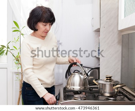 Mature woman doing completing   chores in   kitchen.