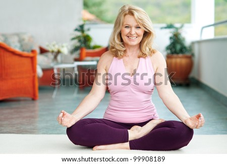 mature woman doing lotus yoga position on her home balcony - stock photo