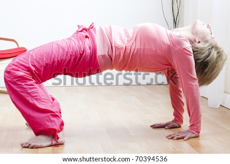 Mature Woman doing the five tibetan rites; fourth rite - stock photo