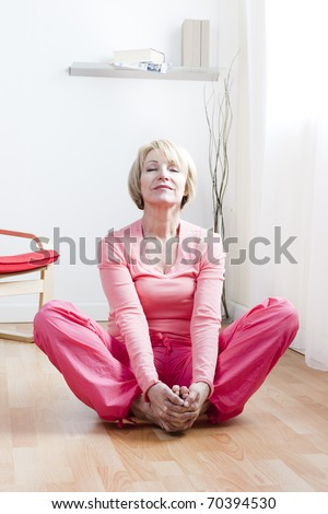 Mature Woman doing yoga exercises - stock photo