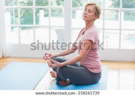 Mature woman doing yoga on fitness mat at home in the living room - stock photo