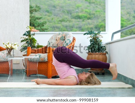 mature woman doing yoga position on her home balcony