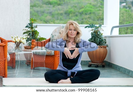 mature woman doing yoga position on her home balcony - stock photo