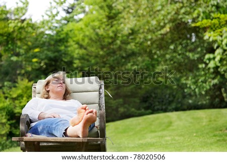 Mature woman dozing in a garden chair - stock photo